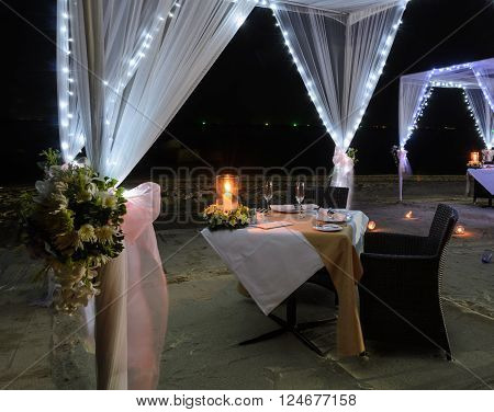Romantic dinner table with white tent for a couple on tropical beach at night