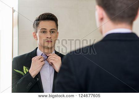 businessman looking in mirror fixing hie tie