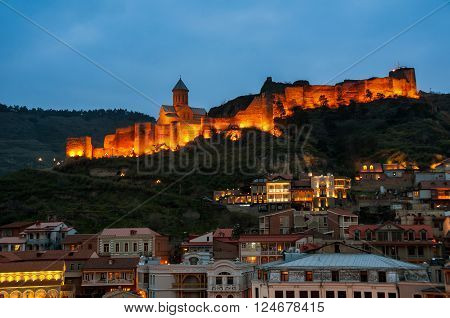 Aerial night view of Old Tbilisi Georgia with Illuminated Castle and cloudy blue sky