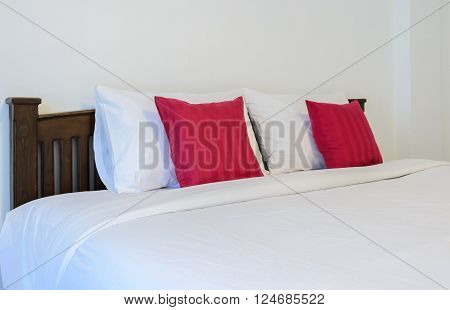 White bedroom with tidy King size bed and red pillows