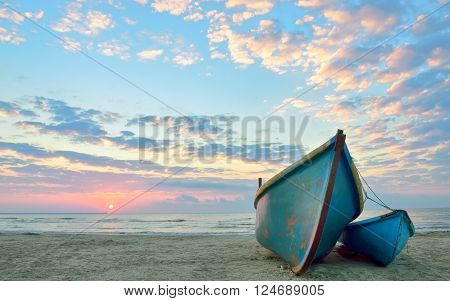 sunrise over an old wooden fishing boats