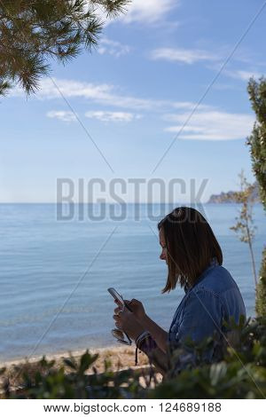 Side view of adult woman using cell phone while sitting against of waterscape