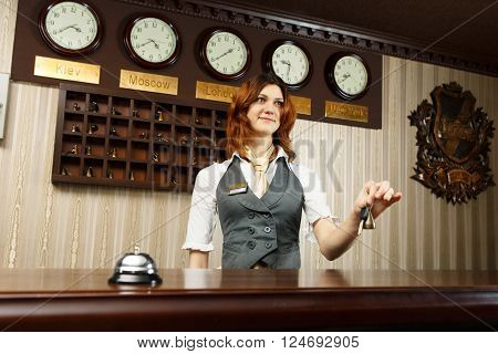 Hotel reception. Female receptionist at reception gives key to a guest. Modern hotel reception counter desk with bell. Woman receptionist at desk. Travel, hospitality, hotel booking concept. poster