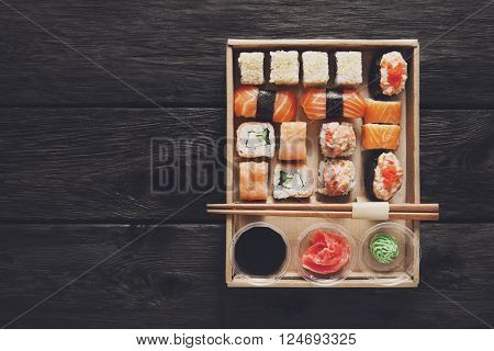 Japanese food restaurant, sushi maki gunkan roll plate or platter set. Free, copy space, chopsticks, ginger, soy sauce, wasabi. Sushi at rustic wood background in take away, delivery box. Top view.