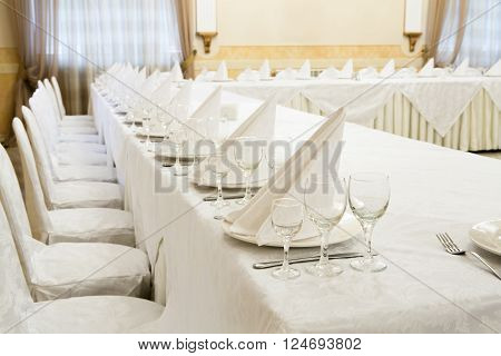 Beautifully organized event - served festive white tables ready for guests.  Event in restaurant. Banquet, wedding decor, celebration. Catering and event. Wedding tables. Large restaurant hall.