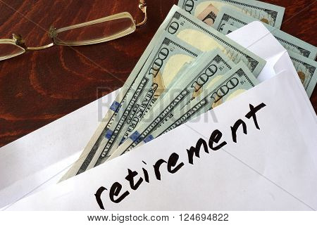 Retirement written on an envelope with dollars. Savings concept.