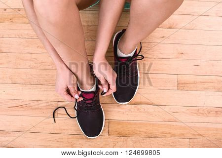 Top view photo of young sporty woman. Fitness girl sitting on floor and tying shoelaces. Focus on sneakers