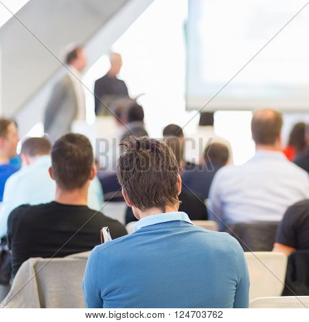 Presentation in lecture hall. Speeker having talk at public event. Participants listening to lecture. Rear view, focus on man in audience.