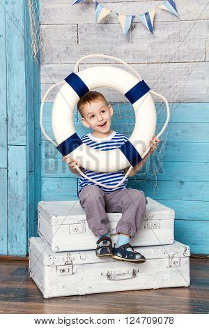 Little boy sitting on a suitcase and holds the lifeline, looking away