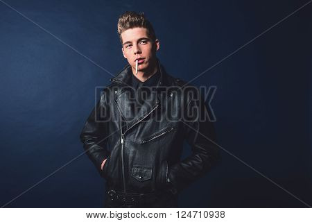 Cigarette smoking retro 50s rock and roll fashion man wearing black jacket and jeans.