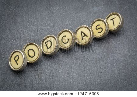 podcast word in old round typewriter keys against gray slate stone