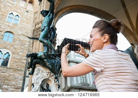 Seen From Behind Woman Taking Photo Of Statue Of Perseus, Italy
