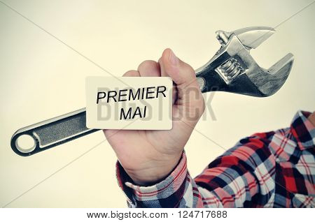 closeup of the hand of a young caucasian worker man with an adjustable wrench and a signboard with the text premier mai, may day in french