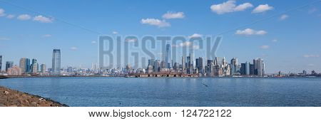 This sweeping panorama contains views of Jersey City and Manhattan as seen from Liberty State Park. From left to right you can see the Goldman Sachs Tower 432 Park Avenue Freedom Tower with Ellis Island in front and the Brooklyn Brid