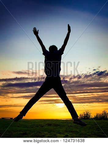 Happy Man Silhouette jumping on the Sunset Background