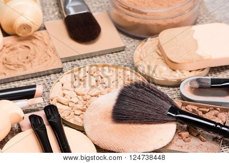 Makeup products to create the perfect complexion. Correctors, foundation, powder, bronzer with brushes and cosmetic sponges on sackcloth