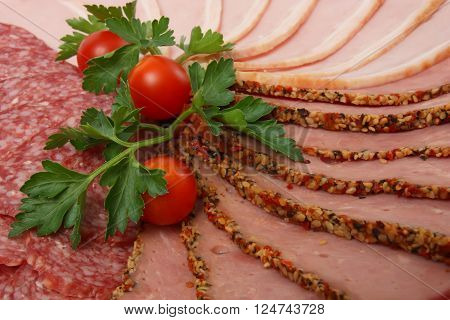 Slices of salami ham and beef decorated with parsley and cherry tomatoes close-up