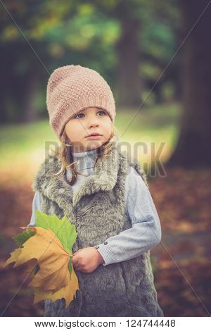Beautiful young girl having fun in the park with lovely autumn colours