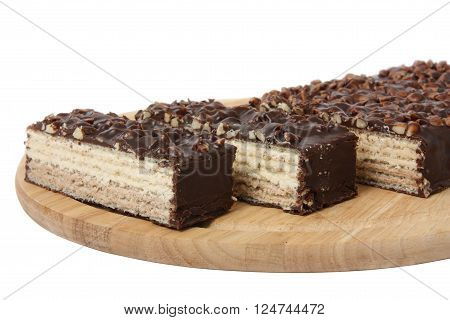 Waffle cake with nuts and chocolate on wooden board, isolated on white background