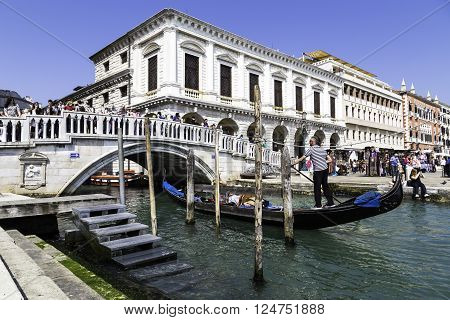 VENICE ITALY - APRIL 23 2015: Traditional gondolier rowing through the channels. Gondola trip during the ride in Venice Italy. Traditional Venice gondola ride.