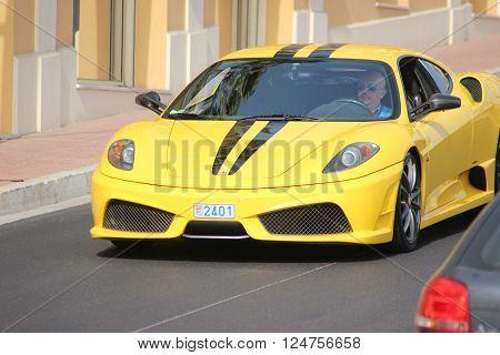 Monte-Carlo Monaco - April 6 2016: Ferrari 430 Scuderia on Avenue d'Ostende in Monaco. Man Driving an Expensive Yellow Ferrari 430 Scuderia in the south of France