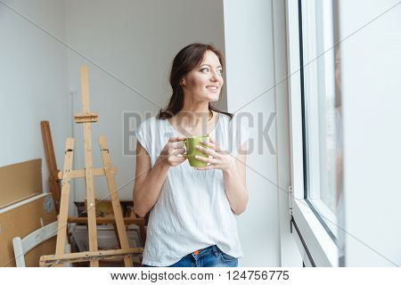 Smiling pretty woman artist drinking coffee near the window in workshop