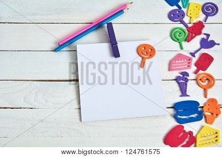 Note book with  pencil on wooden background and fanny cartoon food