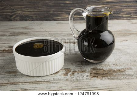 Grape molasses in bowl and glass pitcher on wooden background.