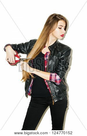 Cool beautiful teenage girl in black jeans, black leather jacket and red plaid shirt with long blonde hair holding her hair and cutting it with scissors. Isolated on white background, retouched.