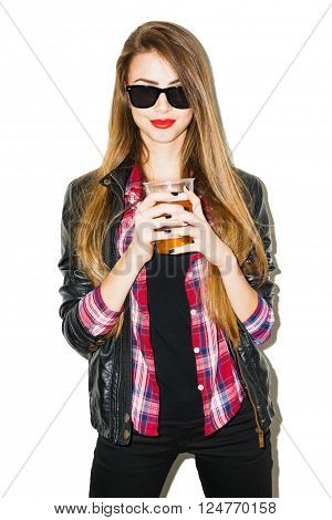 Cool teenage girl with sunglasses and long blonde hair, wearing red plaid shirt, black leather jacket and pants, drinking beer from plastic glass. Isolated on white background. retouched.