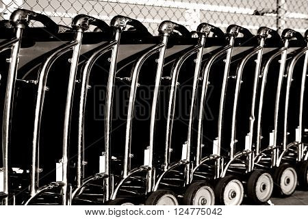 Baggage car of a luggage cart rental are consecutively ranked on the sidewalk and the entrance of an airport.