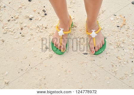 Green flipflop sandals on sea beach, Thailand