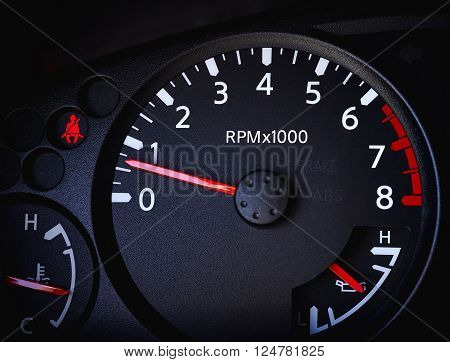Close of up car tachometer with temperature gauge battery gauge and seat belt warning light