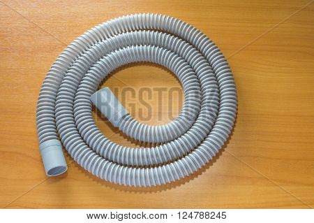 Single CPAP hose on wood table shown without mask and machine