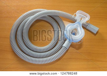 CPAP mask attaching to the air hose use with CPAP machine to help patients with sleep apnea problem showing the inside side of the mask displaying on wooden table