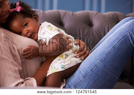 Woman relaxing with her toddler daughter, mid-section crop