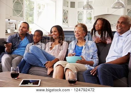 Multi generation black family watching movie on TV together