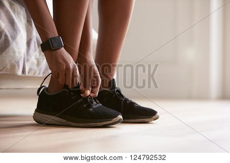 Young black woman tying sports shoes, close-up