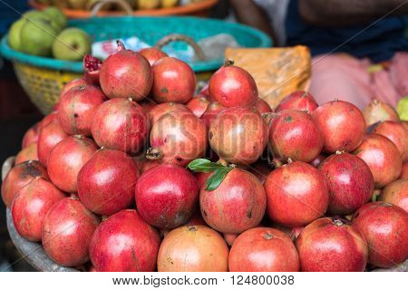 A pile of beautiful organic burgundy pomegranates in a market