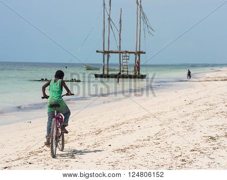 PAJE ZANZIBAR - MARCH 30 2016: Local boy biking on the beach in Zanzibar Tanzania.