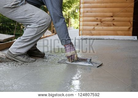 Mason leveling and screeding concrete floor base with square trowel in front of the house. Construction business, do-it-yourself, precision work around the house concept. poster