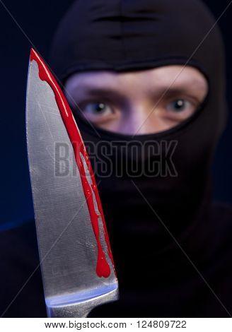 Man criminal in black mask with knife over dark blue background