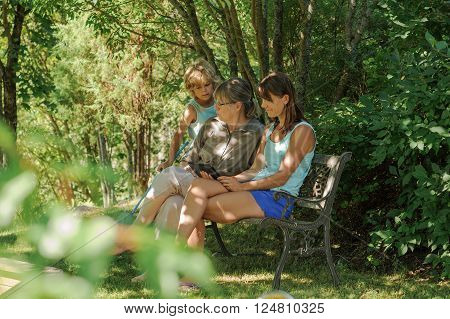 3 Generations. Grandmother, mother, and son in garden. The women are sitting on a bench and looking at a tablet. Young boy is carrying a butterfly net and looking at the tablet.