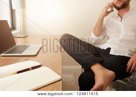 Diary and laptop on desk with businessman sitting in background making a phone call. Home office worktable.