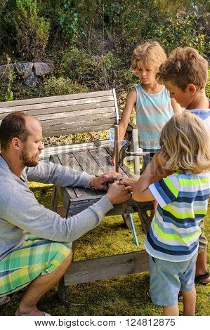 Father shows his 3 sons how to make a sailing boat from pieces of wood. They're outdoors