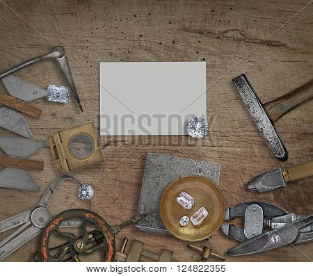vintage jeweler tools and diamonds on a bench, space for text on business card