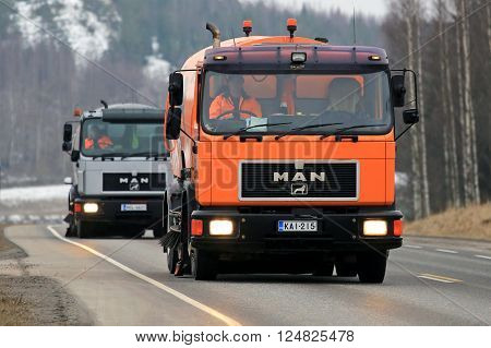 SALO, FINLAND - MARCH 24, 2016: Two MAN Schorling Road Sweeper trucks drive along highway in Salo. Modern street sweepers are mounted on truck bodies and can vacuum debris that accumulates in streets.