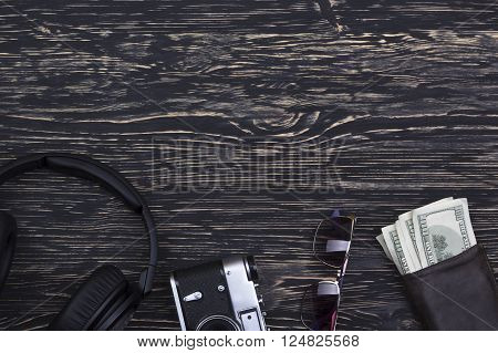 Men's accessories: wallet, headphones, sunglasses and camera on wooden background