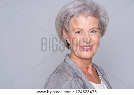 Portrait of a smiling senior woman in front of gray background