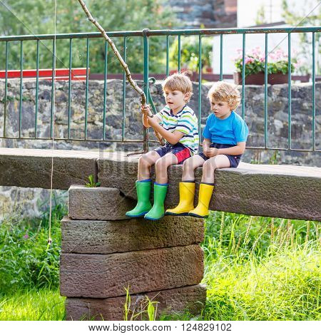 Two adorable little friends  fishing on a river with selfmade fishing rod  on sunny summer day. Happy children having fun. Active leisure for children outdoors.
